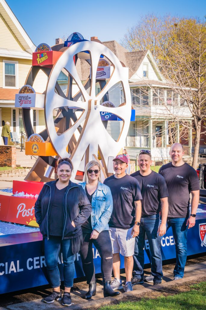 Group of Post employees standing in front of a parade float.